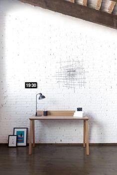 Escritorio de @puntmobles de dimensiones ajustadas para configurar un espacio de trabajo íntimo, cálido y ordenado. El sobre tiene un hueco/plumier con puerta practicable para guardar la tableta, el ordenador, los lápices, el papel o pequeños recuerdos.  Tiene un atril desmontable.  Está realizado en madera de roble y nogal. Las patas traseras tienen una ranura para encajar y subir los cables, los cuales se recogen en un hueco de la parte inferior del sobre de trabajo.