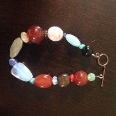 "Multicolored beaded bracelet Has varying shades of green beads, burnt orange, light tan, blue, red, dark brown, black and clear.  Only one bead has an imperfection (see pic #3). Matches a variety of clothing. I've only worn a few times. Fits a 6"" wrist with a couple extra inches to spare. Jewelry Bracelets"