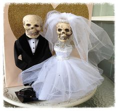 A gorgeous table centerpiece features a skull on a wire frame bodice covered with layers of lovely tulle. Trimmed with a pearl and tulle veil.  The