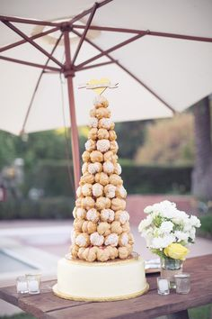 Croquembouche atop a wedding layer cake for cutting | This Love Of Yours Photography - thisloveofyours.com | On #SMP here: http://www.StyleMePretty.com/2014/03/29/whimsical-california-ranch-wedding/