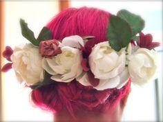 Diadema de flores blancas y detalles en rosa con recogido trenzado en cabello rosa fucsia.