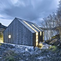 Designed by architects TYIN tegnestue, the building is made of materials that were salvaged from a dilapidated boathouse on the site, plus new grey-patinated pine.