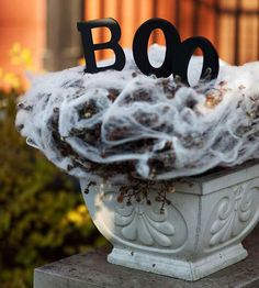 Create your own spooky outdoor spiderweb planters from stretched and pulled cotton balls fitted over plants. Spell out a Halloween message with black foam letters attached to small dowels using adhesive, and stick them into the plant.