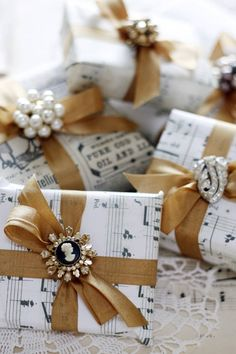 LOVE this gift wrap idea! This could work for Christmas, Mom's Day AND Bridesmaids!! Wrap gifts  in old sheet music and vintage newspaper clippings. They were finished with ribbon and sparkly jewellery. If you have a music stamp you could do your own paper