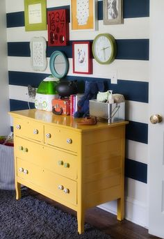 Bright Nursery, wall decor, clock, striped wall, navy, white, green, red, yellow, colorful frames, yellow dresser: