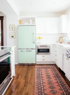 This mint colored fridge takes the cake in this dreamy white kitchen.
