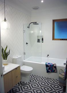 Stunning bathroom featuring Phoenix Tapware matte black taps and wonderful pattern tiles and towels #tilebathrooms