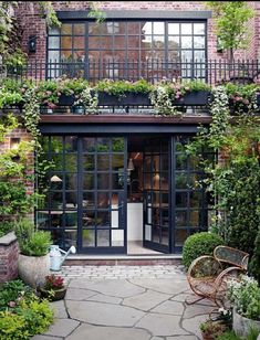 Beautiful New York courtyard with lots of style, glass, and plants. #courtyard #outdoorliving #wallofwindows #blackframewindows
