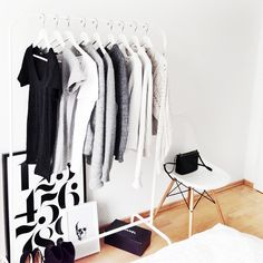 Black t-shirts + grey sweaters + white tops on a clothing rack