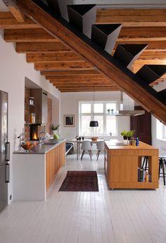 EKSPONERTE DRAGERE: Flere rom ble slått sammen for å danne ett stort allrom. Takbjelkene er blottet for å gi økt takhøyde som passer bedre til det nye rommets proporsjoner. Kjøkkenet er produsert av Stein Haanshuus på Røros.