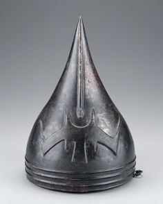 """Bronze helmet with """"lightning flash"""" insignia and vertical raised band terminating in a dragon's head on front. Three horizontal raised bands at rim. 