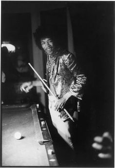 Jimi Hendrix shooting pool at the home of John and Michelle Phillips.
