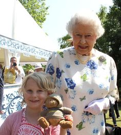 12 JULY 2013 The Queen surprised all when she happily posed for a photograph with seven-year-old Jessica Fitch at the Coronation Festival.  She kindly obliged the young girl, who was clearly thrilled with the opportunity and beamed away at the camera. Jessica even made sure her little teddy bear, Bertie Bear, was included in the treasured snap.