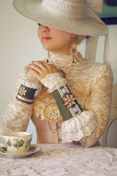 Steampunk Victorian Tea Party Cuffs: Sage green fabric with Shabby Chic eyelet lace feature a small steampunk clock & pink enamel flowers mounted upon antiqued brass filigrees. One cuff is longer than the other for a neo-Victorian twist, via Etsy.