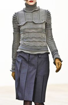 Pringle of Scotland love.  Grey turtle-neck sweater, navy skirt. Pleats. Knee-length.  Gloves.