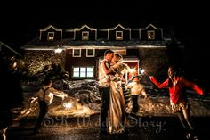 Bride & Groom kissing with sparklers in front oft Bally Spring Inn Photographed by Wedding Photographer Sam Rodriguez with S.R.WeddingStory Wedding Photography. #sparklers #kissing #bride #groom #wedding #snow #ballyspringinn