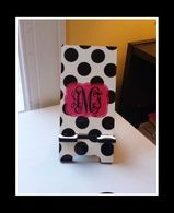 This phone stand has white with black polkadots, hot pink whimsical frame, and a black monogram with vine script.