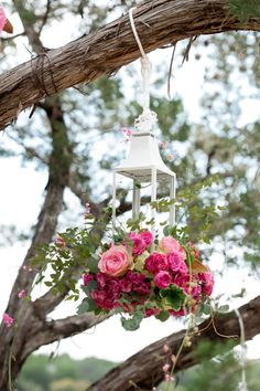 Hanging Lantern Holds Flowers at an Outdoor Wedding