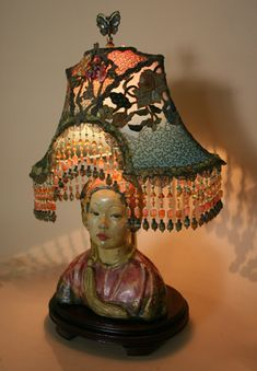 Wonderful antique chalkware statue base by artist E. Hunt is adorned with a exotic Napoleon lampshade with antique Chinese embroidery and vintage dogwood silk flowers. The colors go from dusty pink to green. Hand beaded fringe in matching tones. Lights up beautifully.