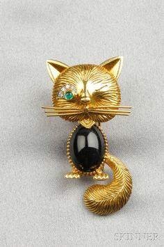 FINE JEWELRY - SALE 2601B - LOT 18 - 18KT GOLD GEM-SET CAT BROOCH, VAN CLEEF & ARPELS, NEW YORK, WITH A BLACK ONYX CABOCHON BODY, CABOCHON EMERALD EYE, SINGLE-CUT DIAMOND M - Skinner Inc