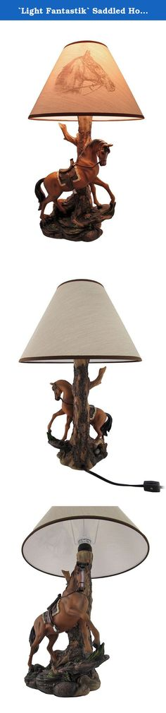 `Light Fantastik` Saddled Horse Table Lamp With Printed Fabric Shade. This remarkable table lamp features a beautiful saddled brown horse standing proudly upon a boulder. A tall tree trunk forms the stem of the lamp to hold the light fixture which will support one `type A` light bulb up to 45 Watts (light bulb included with purchase). Made from cold cast resin, the base of the lamp features hand painted accents which highlight the excellent detail from the gnarled tree bark to the frills…