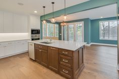 Kitchen: hardwood floors, stained island cabinets, painted cabinets, quartz counters, stainless steel appliances, ceramic tile backsplash