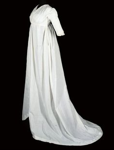 c1795-1800 white round gown, white muslin with simple vandyked self-trim to hem and open edges, pleated sleeve detail and under-bust tie, the bodice lined in white linen. Christies.
