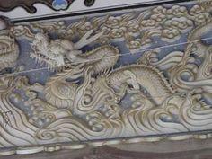 西往寺の龍    年代:明治18(1885)年  作者:安田鹿市、児島嘉六 (いずれも西往寺の墨書による)  場所:仁摩町仁万   仁摩漁港の近く、古い町並みを残す一角にある西往寺。向拝(本堂のひさし)の下に迫力ある作品群が見るものに迫ってきます。作品群とは、中央の「龍」と両側の「安珍清姫」「金毛九尾の狐」。そのなかでひときわ力強い作品が、中央の雌雄の「龍」。幅3.8メートル、高さ1.2メートルの大きさで漆喰塗りの額縁の中に納められています。