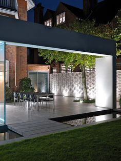 Innovative modern extension including glass facades and external reflecting pool. The extension to a traditional Arts and Crafts detached 600m2 house incorporates a contemporary garden design creating unique indoor-outdoor living space. Wimbledon Architects