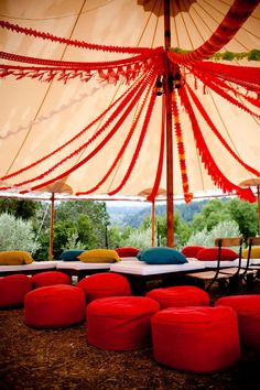 The firetruck red streamers, mustard and teal pillows create a lively but relaxing theme to this outdoor tent. I think this is a beautiful and comfortable setting for an outdoor wedding.