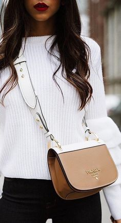 White cable knit sweater, black jeans, and a light brown side bag.