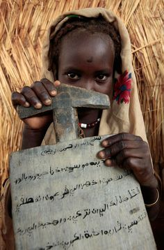 """Africa   """"Children from Darfur"""".  A little girl from Sudan's Darfur with a scarf on her head holds her slate after a koranic class in Arabic in a Birao's district, Vakaga prefecture, north-eastern CAR.   ©Pierre Holtz for UNICEF"""
