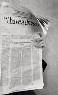 "Black and White image of someone behind a newspaper with headline, "" I have a dream..'"