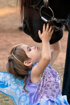 her first horse.....adorable younf girl in fairy costume kissing large draft horse.