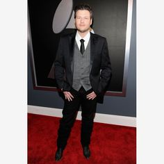 "Blake Shelton looks dapper in this gray and black suit worn at the 2012 Grammys. This newlywed showed no sign of nerves before his Grammy performance and tribute to Glen Campbell, keeping with his ""cowboy"" stance. This country artist's outfit wouldn't be complete without his slick, black cowboy boots to go with his suit. Yee-haw!"