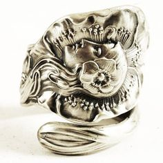 Nice and hefty Sterling silver spoon ring, this ring depicts a very 3-dimensional and high relief profile of a womans face with a poppy in her hair. Fashioned in the Art Nouveau style as graceful and flowing hair drapes down this design. This woman seems to be calm as a kitten as a giant