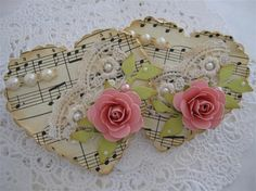 Shabby chic - Valentine's Day - scalloped edge hearts cut from aged sheet music, embellished with lace, pearls, pink paper hearts, and sage green paper leaves - lovely! I think if I were making these, i'd cover perhaps the bottom third or 2/3 with the lace, maybe tinier pearls following a curve if any are attached to the paper alone, or perhaps a couple of seed pearls scattered. Very nice!