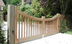Wooden Driveway Gates-simple, and warm with apple/snake metal latch in the middle...cement posts and dry stack along road