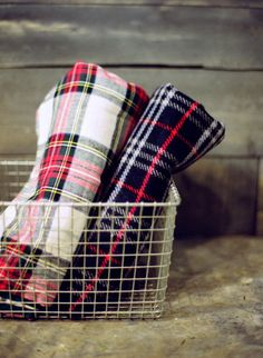 folded plaid throws in metal basket