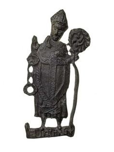 Pilgrim badge from a shrine of St Leonard, probably in England. This badge depicts a standing figure of St Leonard. He wears a bishop's vestments and mitre. In his left hand is a crosier (its shaft is slightly bent) and his right hand is raised in a gesture of blessing. Fetters hang from his right wrist. He is standing on a scroll with an inscription: 'S LENARD'. Production Date: Late Medieval; 14th-15th century