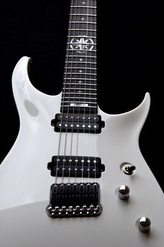 White customized with custom star inlay pattern and North Star fret inlay. Guitar has Hannes bridge, pure white color and control layout where toggle is front of other control knobs. Body customized with SHRECUT-cutaway and slim body outline thickness