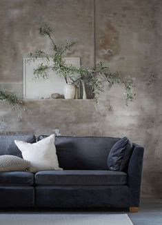 We love the contrast between our Moleskin Simply Velvet fabric, the sleek Mid-century style sofa and the worn rustic limestone walls | We're all about that high and low mix - seen here an IKEA Stockholm with a Bemz cover in Daniella Witte's stunning minimalist studio