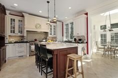 Large natural wooden island here features bar style seating, doubling as an in-kitchen dining area.
