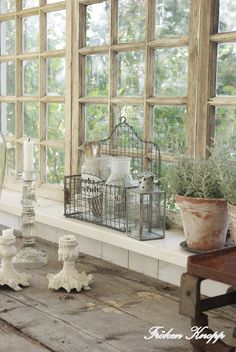 love the combination of the windows, white washed built in bench and metal lantern and baskets.