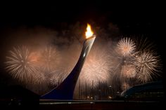 Fireworks explode behind the Olympic torch after it was lit at end of the opening ceremony for the 2014 Winter Olympics in Sochi