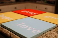 painted canvas using chipboard letters for stencils