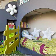 Ein Garten im Kinderzimmer – der Teppich in Rasen-Optik, die Blumen an der Wand und das gelbe Gatter am Hochbett vermitteln Outdoor-Atmophäre pur. Der Vorteil zum echten Garten: Hier kann zu jeder Jahreszeit gespielt werden.