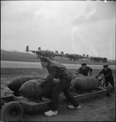 Ground crew of the Royal Dutch Naval Air Service, serving with No. 320 (Dutch) Squadron RAF, push a trolley of 1,000-lb MC bombs to waiting North American Mitchells at B58/Melsbroek, Belgium. Leading Aircraftman Jan Sieben, in the foreground, is wearing 'klompen' (clogs).