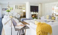 White slipcover sectional sofas and chairs with yellow and navy accents in this coastal beach house - Crisp and clean!!