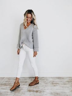 Gray sweater over white jeans.